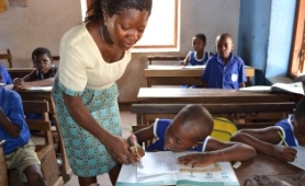 Teacher in classroom with pupil in Ghana.jpg