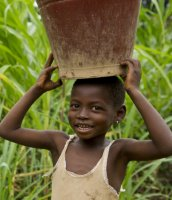 Boy in sub-Saharan Africa carrying a water bucket on his head